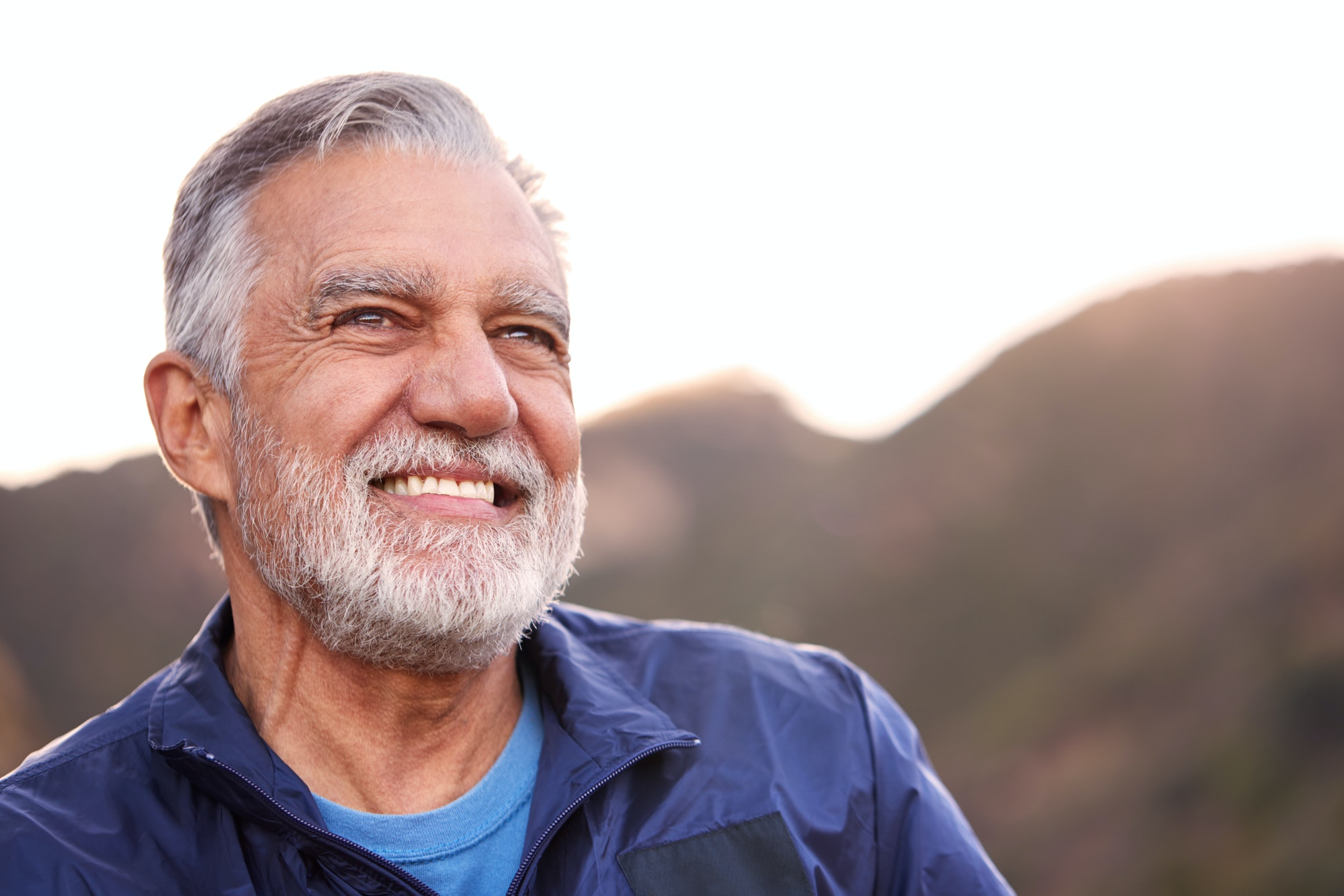 Portrait Of Smiling Hispanic Senior Man Outdoors In Countryside With Mountains In Background